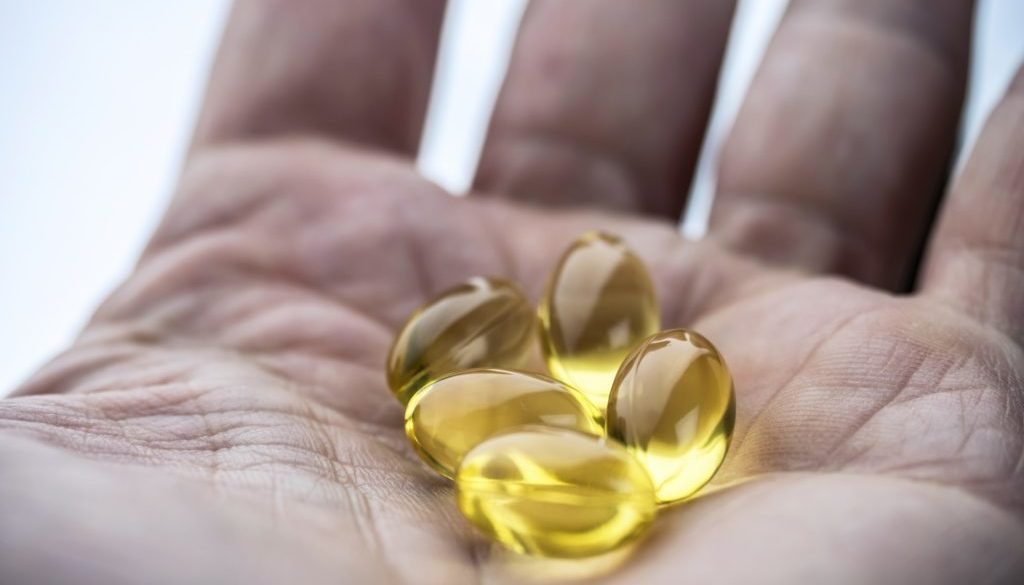 Hand supports several capsules of oil of fish, conceptual image