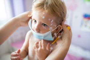 Little girl with chickenpox, mother giving her protective mask
